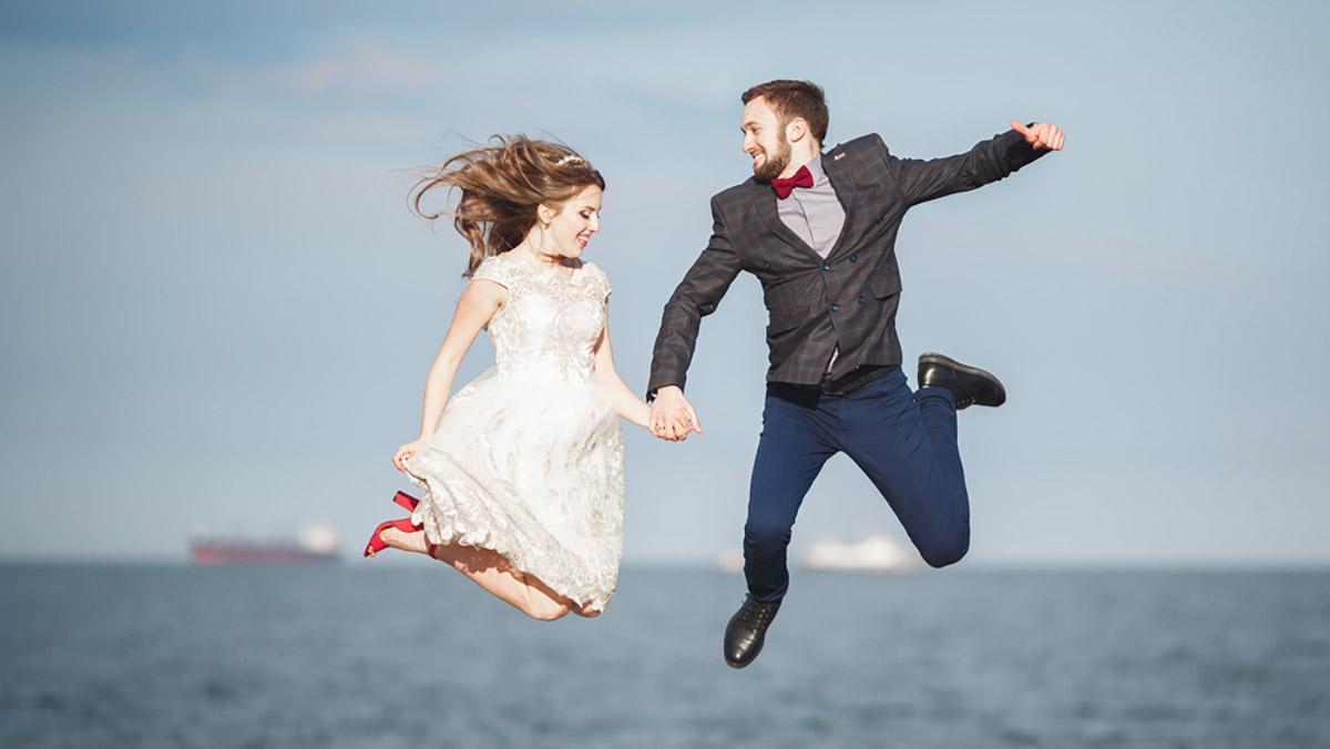 Fröhliches Brautpaar hält sich an den Händen und springt.