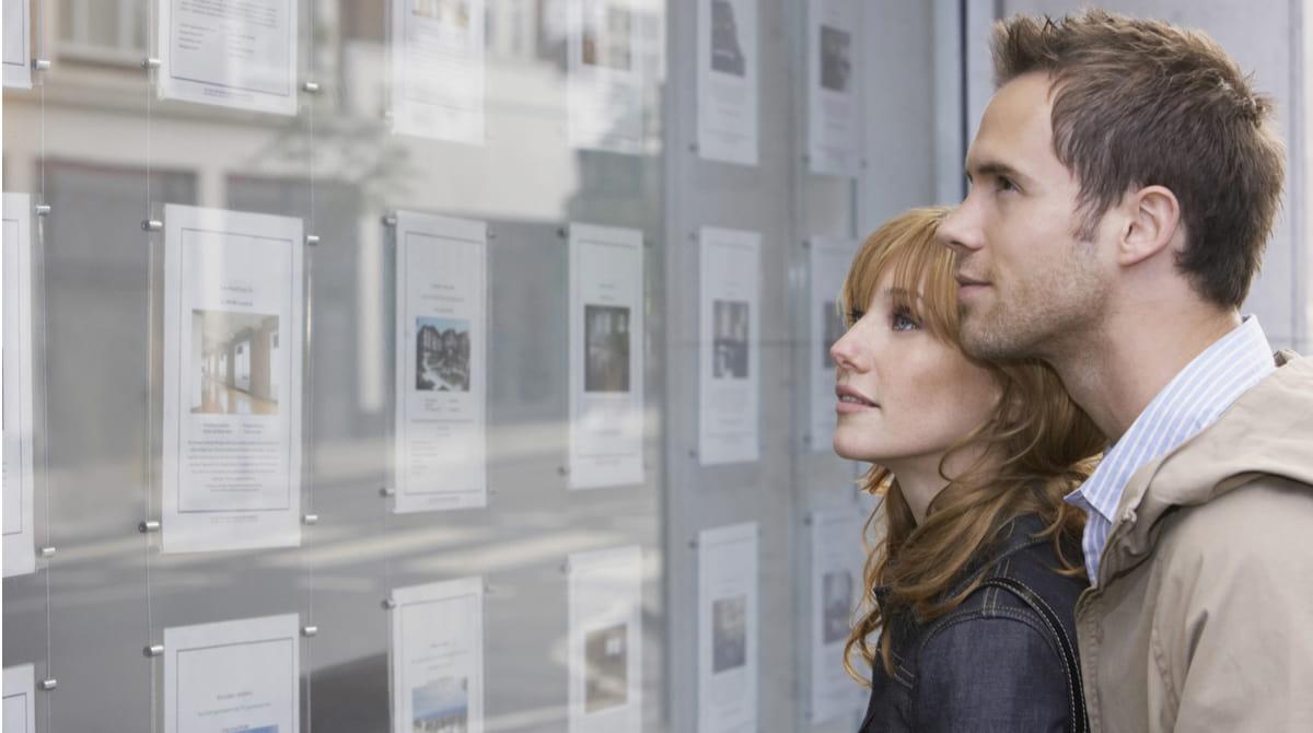 Junges Paar schaut sich Wohnungsanzeigen an.